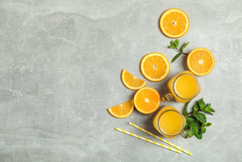 Плоский положенный состав с оранжевыми частями, мятой, tubules и стеклянными опарниками со свежим апельсиновым соком на серой пре стоковые фото