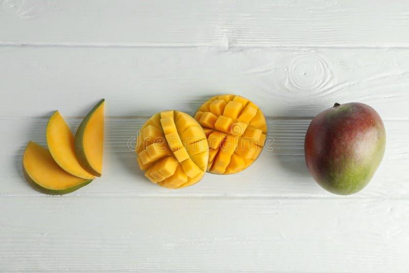 Плоский положенный состав с отрезанными зрелыми манго на белой предпосылке стоковая фотография rf