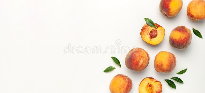 Плоский положенный состав с персиками Зрелые сочные персики с зелеными листьями на белой предпосылке ( r стоковое изображение
