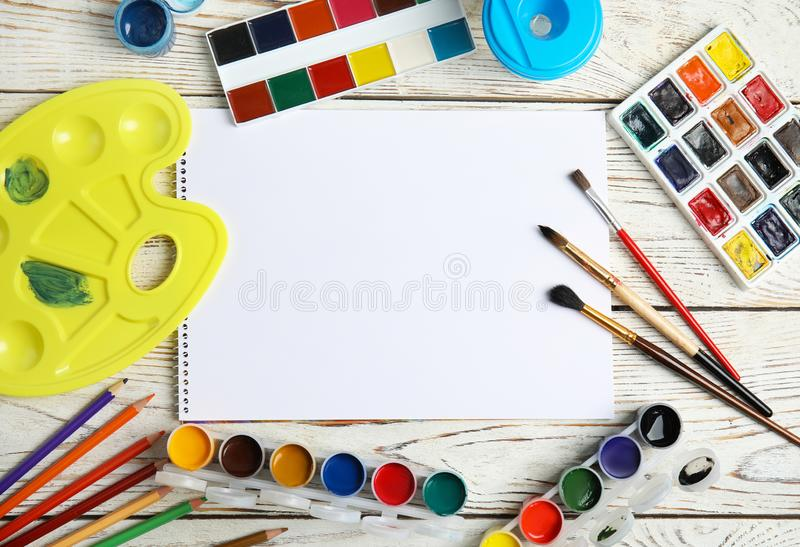 Плоский положенный состав с различными красками, щетками и листом бумаги на деревянной предпосылке стоковое фото rf