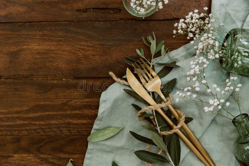 Плоский столовый прибор золота положения, цветки, кольца на linen салфетке, wedding концепция, праздник цветет на деревянном стоковая фотография