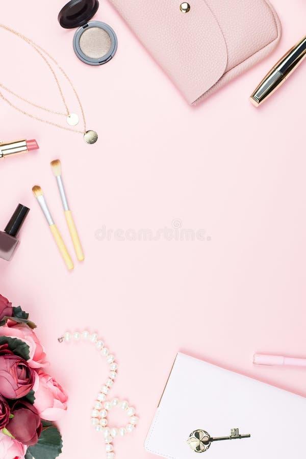 Плоский стол домашнего офиса положения Женское место для работы с блокнотом, аксессуары моды и составляют продукты на розовой пре стоковые фотографии rf