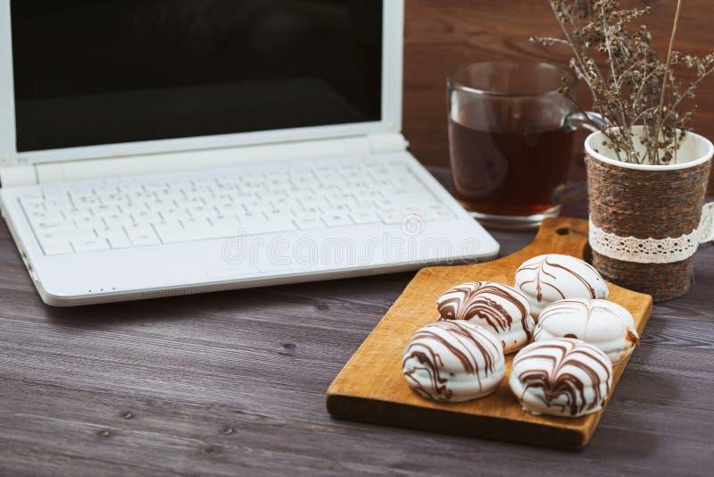 Плоский стол офиса женщины положения Место для работы с компьтер-книжкой, с чувствительными тортами, чай на деревянном столе Пред стоковое фото rf