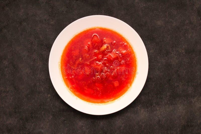 Плоский суп бураков овоща взгляда сверху, на таблице Борщ в белой плите на черном холсте стоковое изображение