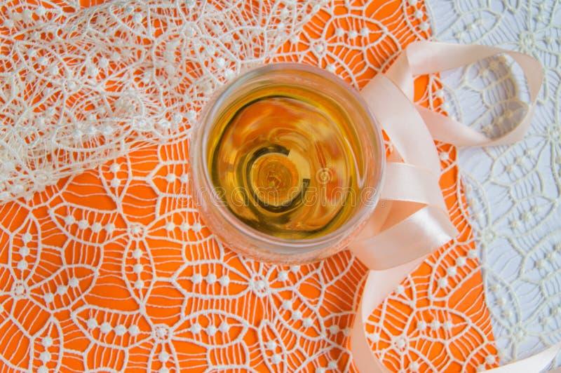 Плоский штабелировать белого вина в стеклянном, бежевом шнурке и декоративной ленте, оранжевой предпосылке, взгляде сверху Романт стоковые изображения rf