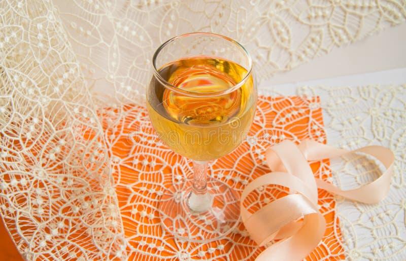 Плоский штабелировать белого вина в стеклянном, бежевом шнурке и декоративной ленте, оранжевой предпосылке, взгляде сверху Романт стоковое фото