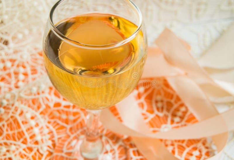 Плоский штабелировать белого вина в стеклянном, бежевом шнурке и декоративной ленте, оранжевой предпосылке, взгляде сверху Романт стоковая фотография