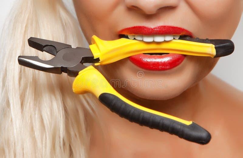 Плоскогубцы в зубах девушки с покрашенной губной помадой красного цвета губ стоковая фотография rf