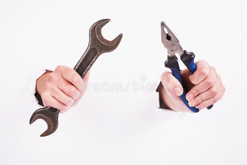 Плоскогубцы и ключ в руке девушки Символ тяжелой работы, феминизма и Дня Труда Изолят на белой предпосылке стоковое фото rf