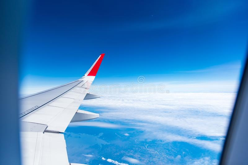Плоское облако bove с голубым небом которые делают фотографию через окно самолета r стоковые фото