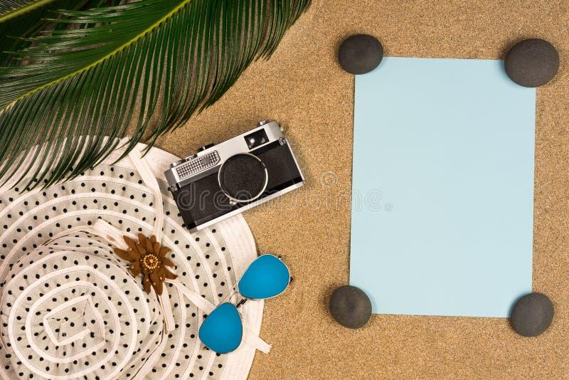 Плоское положение, аксессуары лета взгляда сверху: шляпа, бумага примечания и seashell на пляже стоковая фотография