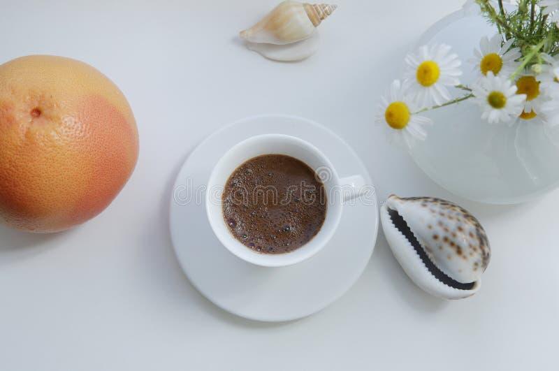 Плоское положение, белая чашка кофе и оранжевые цветки грейпфрута и белых маргаритки на белой предпосылке с элементами дизайна стоковые фотографии rf