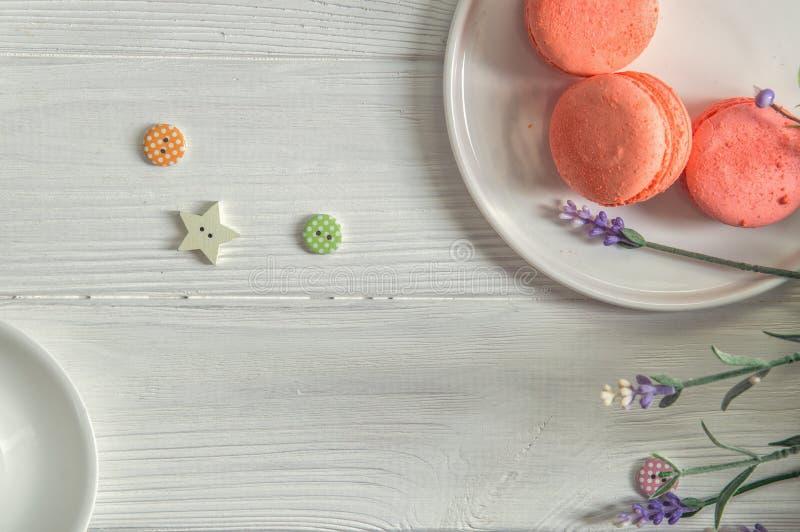 Плоское положение конец вверх Коралл цвета живя Яркие macarons на круглой плите, винтажные кнопки, лаванда деревянное предпосылки стоковое изображение rf