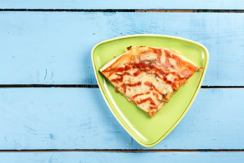 Плоское положение над куском пиццы треугольника свежим на зеленой плите треугольника над голубой таблицей деревянной доски стоковое изображение rf