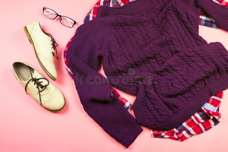 Плоское положение одежд и аксессуаров женщины с фиолетовым свитером, рубашкой проверки, стеклами, ботинками стоковая фотография rf