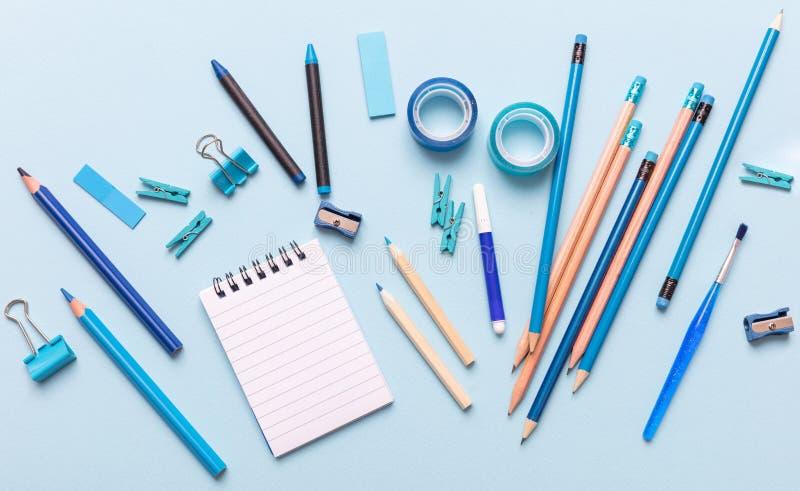Плоское положение офиса, канцелярских принадлежностей школы на голубой предпосылке стоковое изображение