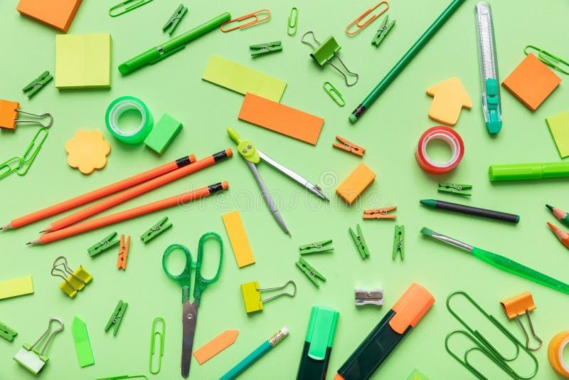 Плоское положение офиса, канцелярских принадлежностей школы на зеленой предпосылке стоковые изображения rf