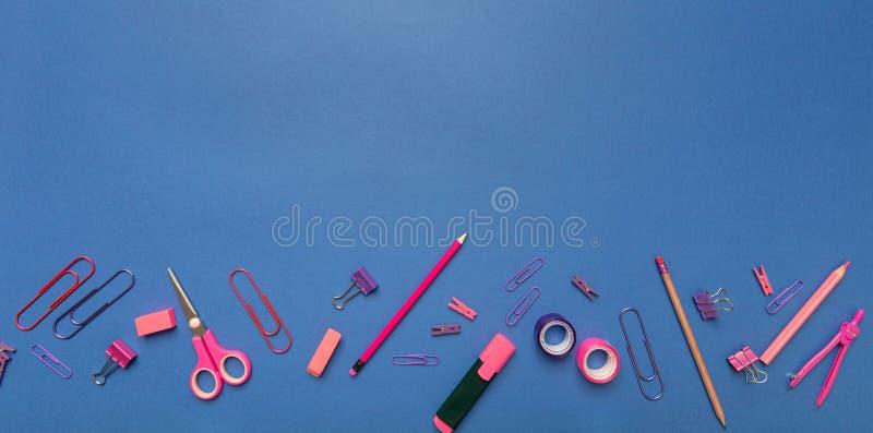 Плоское положение офиса, канцелярских принадлежностей школы, розового цвета на голубой предпосылке стоковая фотография
