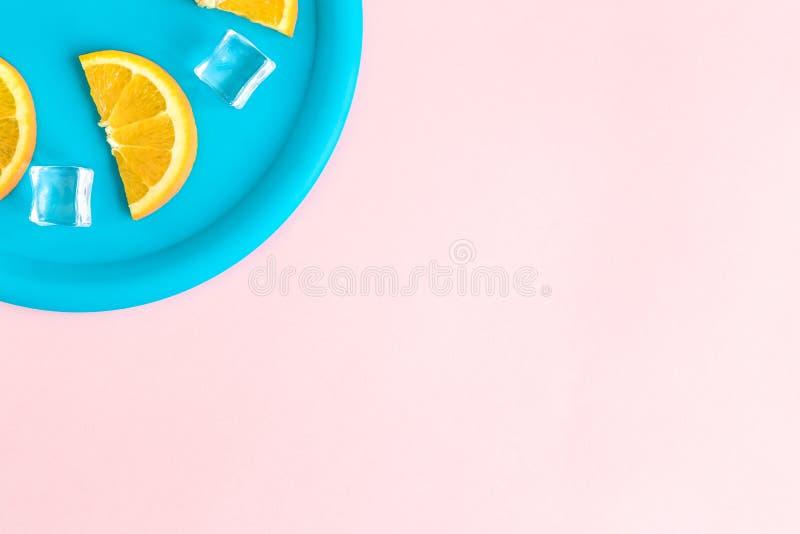 Плоское положение пластиковой плиты с оранжевыми кусками плода и кубами льда против пастельной розовой концепции предпосылки мини стоковая фотография rf