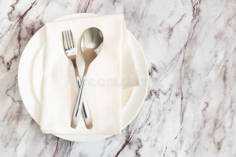 Плоское положение столовый прибор, вилка и нож на салфетке на пустой белой плите на мраморной таблице стоковое изображение