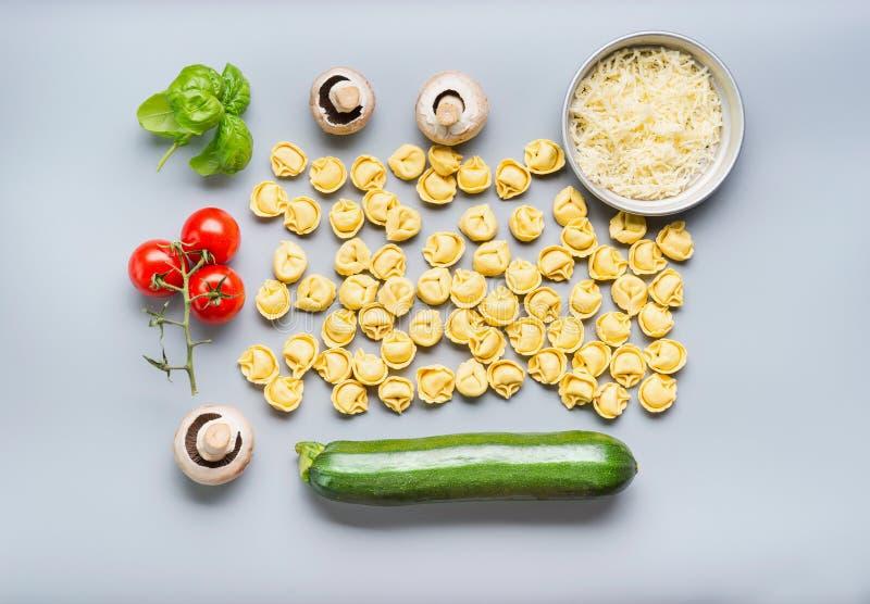 Плоское положение сырцовых макаронных изделий tortellini с ингридиентами для вкусного вегетарианца варя на серой предпосылке, взг стоковые фотографии rf