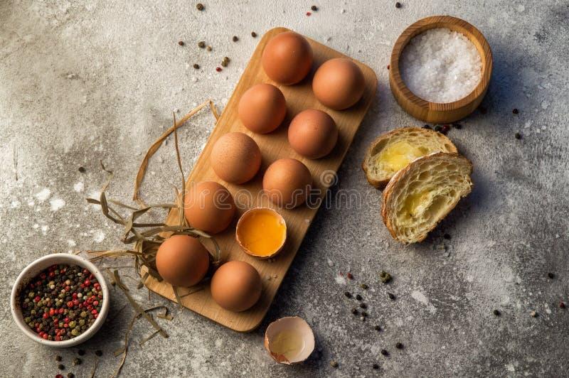 Плоское положение Традиционные яйца фермы завтрака a дюжины в деревянном подносе, рядом с ломтями багета с сыром и специями скопи стоковое изображение