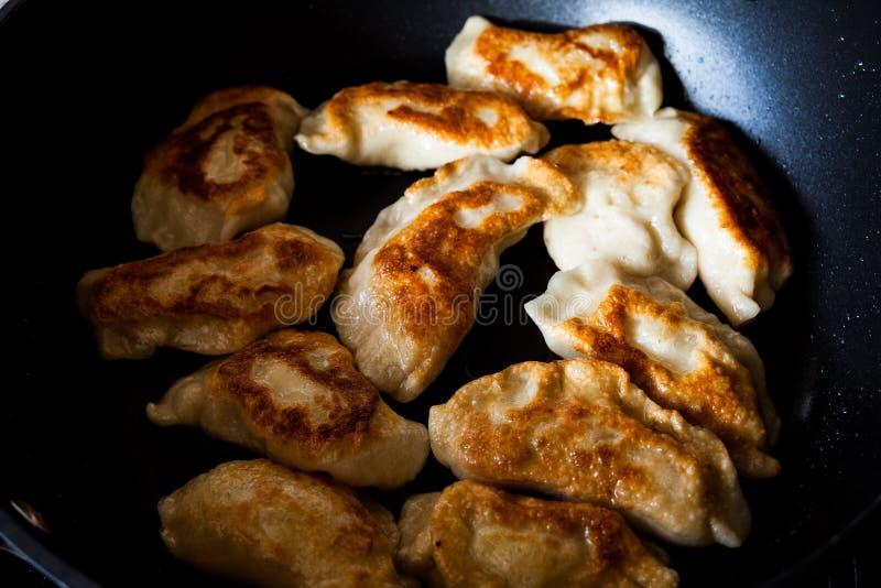 Плоское положенное изображение над традиционным польским pirogi еды в сковороде на таблице Очень вкусная еда теста подготовленная стоковое фото