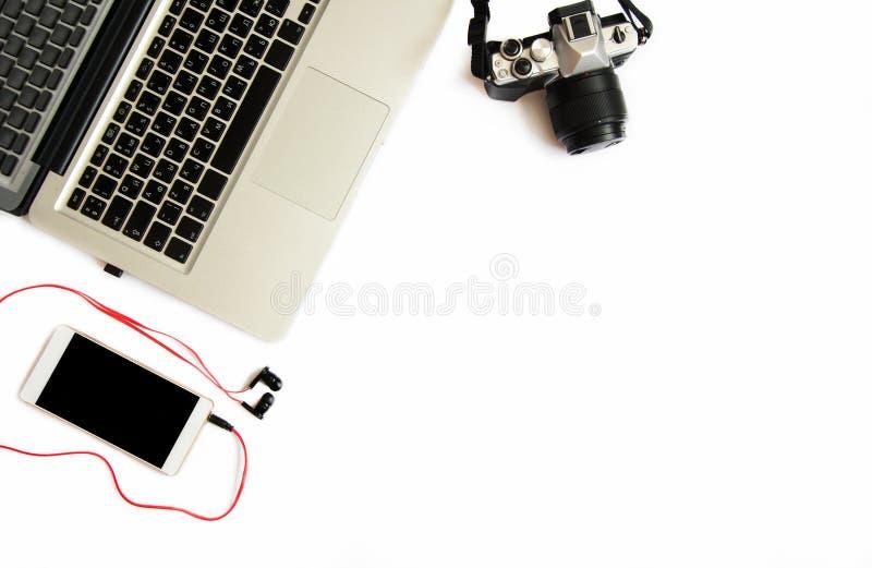 Плоское положенное фото взгляда сверху рабочей зоны фотографа с ноутбуком, шестерней фото и телефоном с наушниками на белой предп стоковое изображение