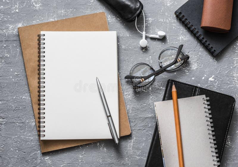 Плоское рабочее место офиса положения Аксессуары дела или образования - пустые стекла блокнота, ручки, карандаши, наушники на сер стоковая фотография rf