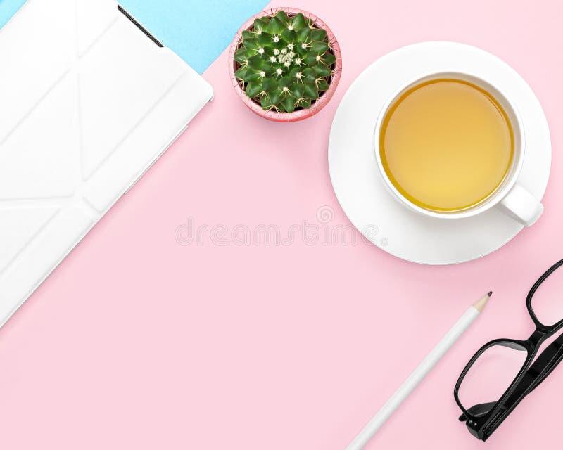 Плоское фото положения стола офиса с предпосылкой планшета, кружки чая, карандаша, кактуса, стекел, розовых и голубых стоковое фото rf