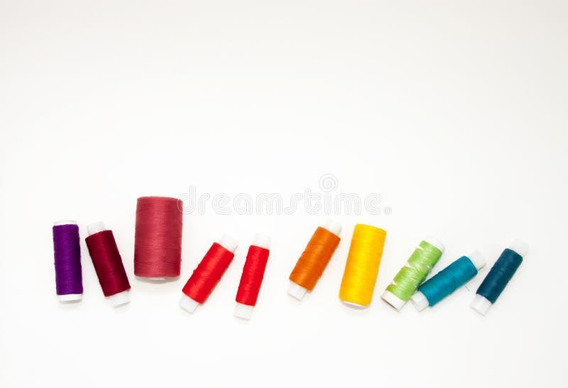 Плоско положите с красочными катышками бумажной нитки, пряжей вышивки, катушками радуги, насмешливыми вверх, взгляд сверху Модель стоковые изображения