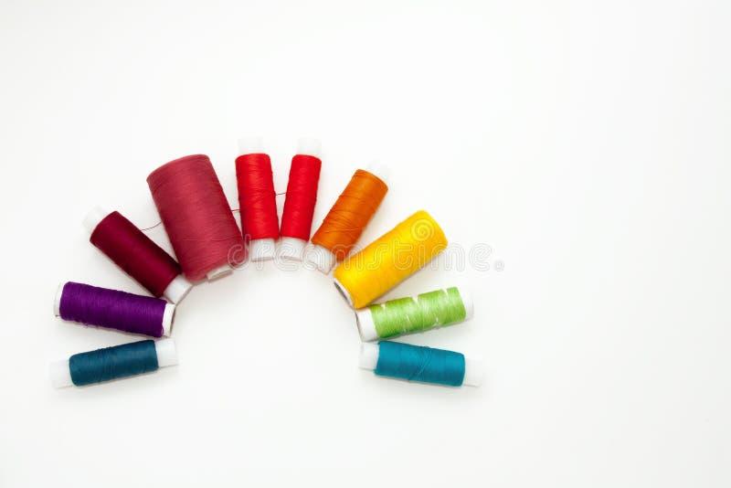 Плоско положите с красочными катышками бумажной нитки, пряжей вышивки, катушками радуги, насмешливыми вверх, взгляд сверху Модель стоковые фотографии rf