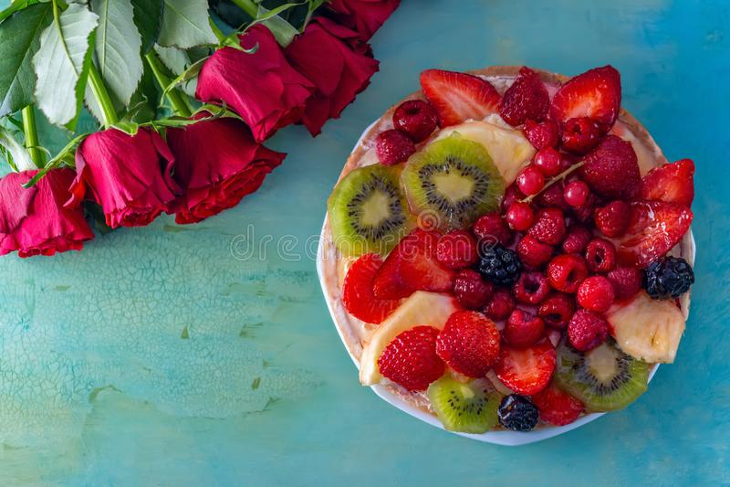 Плоск-положение красных роз цветков и красивого очень вкусного сладкого торта с ягодами на зеленой предпосылке r стоковое изображение
