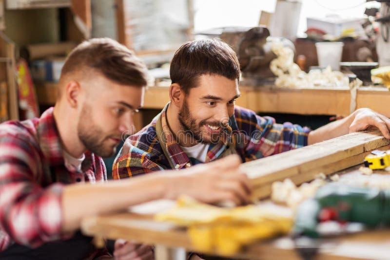 Плотники измеряя деревянную доску на мастерской стоковые фото