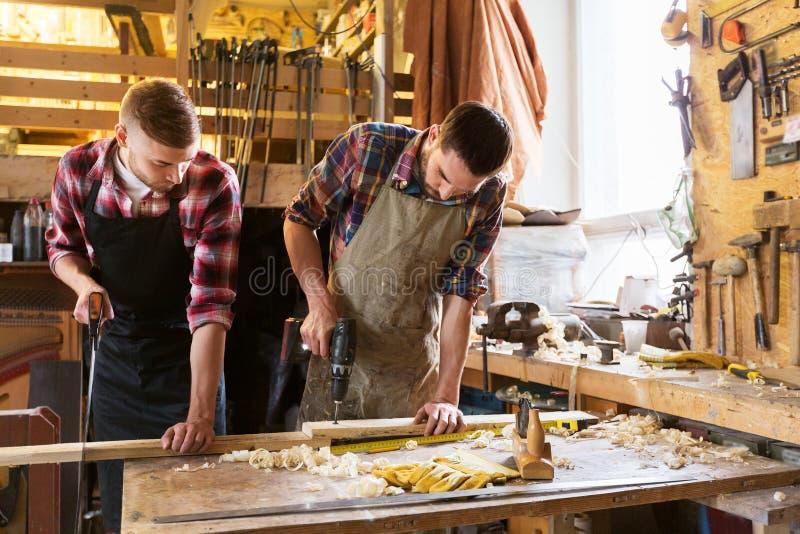 Плотники работая с деревянной доской на мастерской стоковое изображение rf