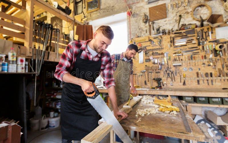 Плотники работая с увидели и древесина на мастерской стоковая фотография