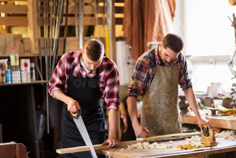 Плотники работая с увидели и древесина на мастерской стоковое фото rf