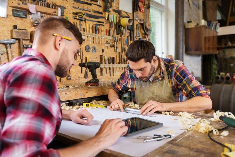 Плотники с планшетом и светокопией на мастерской стоковое фото rf