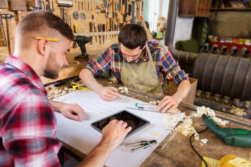 Плотники с планшетом и светокопией на мастерской стоковое изображение rf