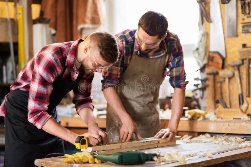 Плотники с правителем и деревянной доской на мастерской стоковые изображения
