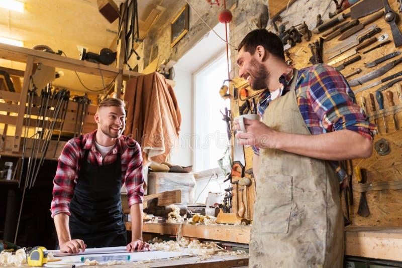 Плотники с правителем и кофе на мастерской стоковое фото