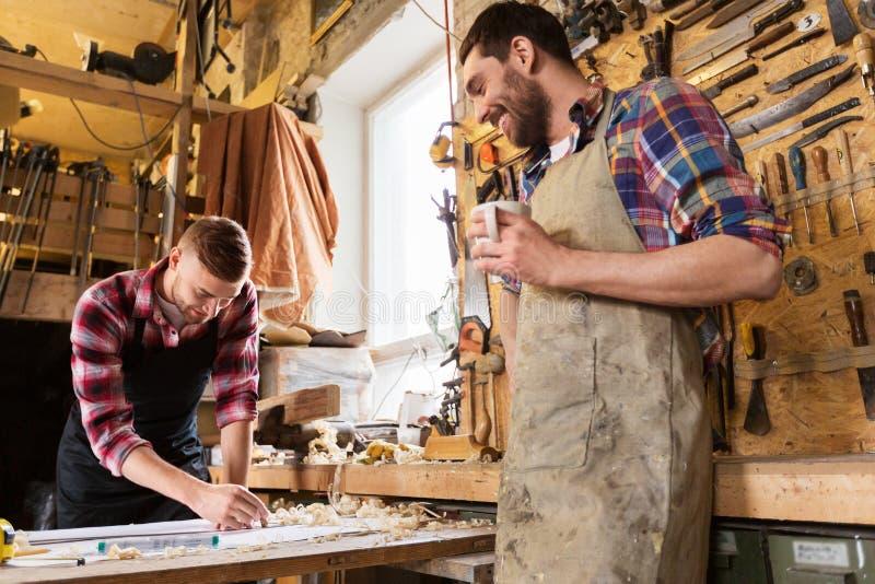Плотники с правителем и кофе на мастерской стоковое изображение