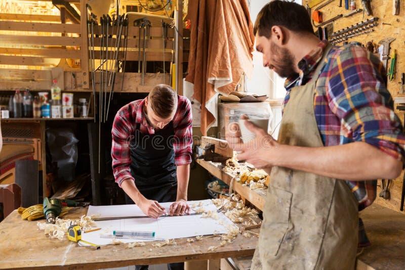 Плотники с правителем и светокопией на мастерской стоковые изображения