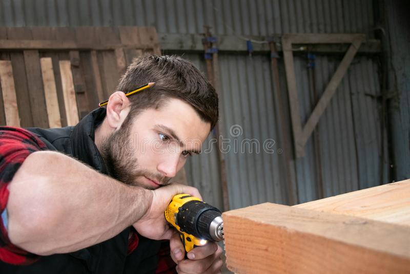 Плотник, деревянная работа работника измеряя, сверля и делая продукт тимберса стоковые фото