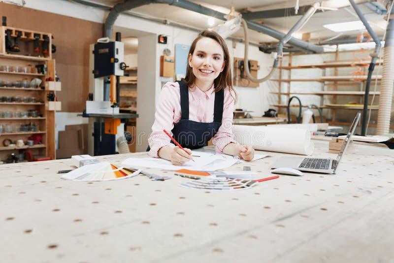 Плотник коммерсантки работая на ноутбуке на деревянной поверхности среди инструментов конструкции Рядом смартфон, ноутбук, доска  стоковое изображение rf
