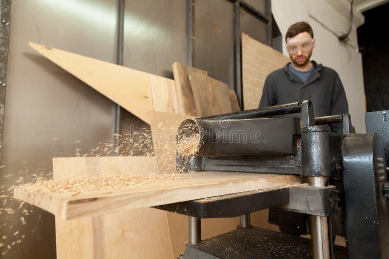 Плотник плотника работая на неподвижном planer силы с деревянным стоковая фотография rf