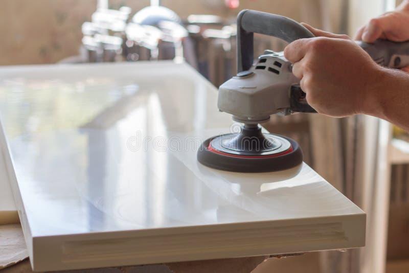 Плотник полирует поверхность фасада перед собирать мебель на запачканной мастерской плотничества предпосылки, выборочную стоковая фотография rf