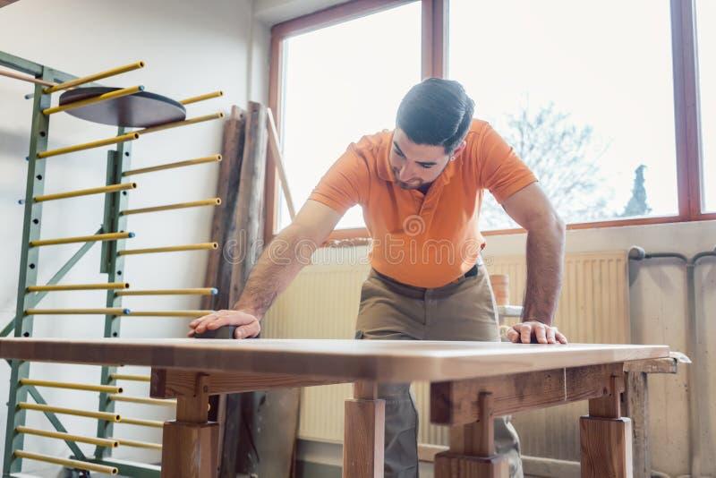 Плотник полируя и лакируя таблицу стоковое фото rf