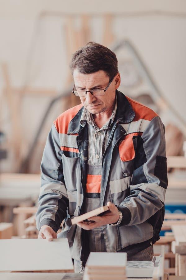 Плотник работает на woodworking механический инструмент Плотник работая на машинах woodworking в магазине плотничества стоковые изображения