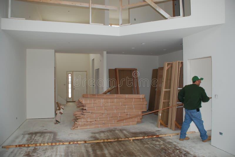 плотник, работающий над окончательным отсечением в здании в средней западной части соединенных штатов стоковое изображение